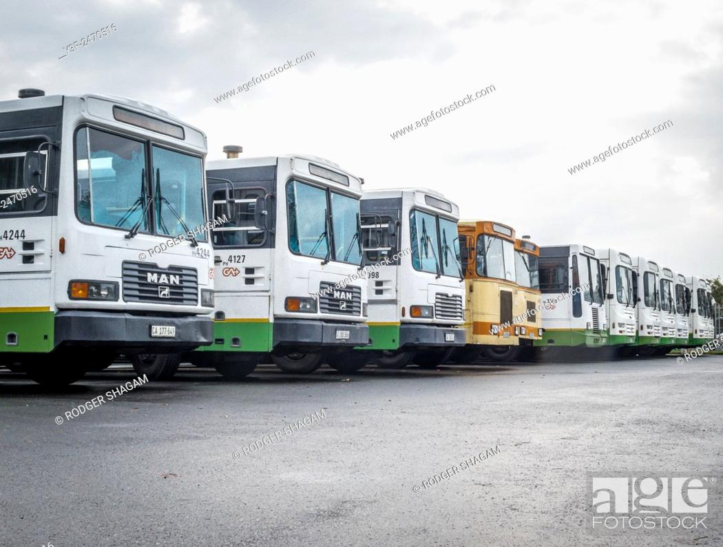 Stock Photo: Busses parked in a row. End of the line. A bus terminus in Cape Town, South Africa.