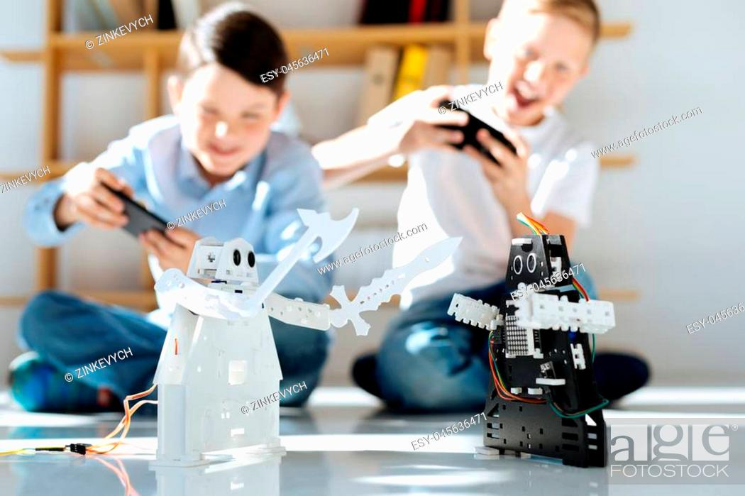 Stock Photo: Excited players. Upbeat little boys sitting on the floor, holding game controllers and playing with their new black and white robots.