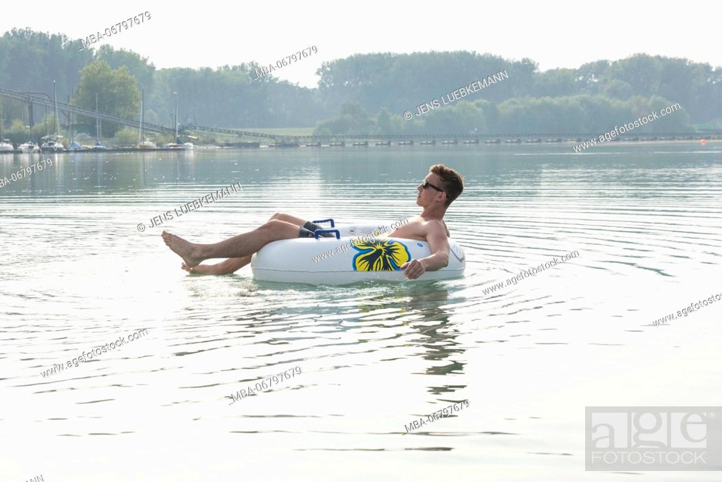 Young man close swim ring in the lake, quarry pond