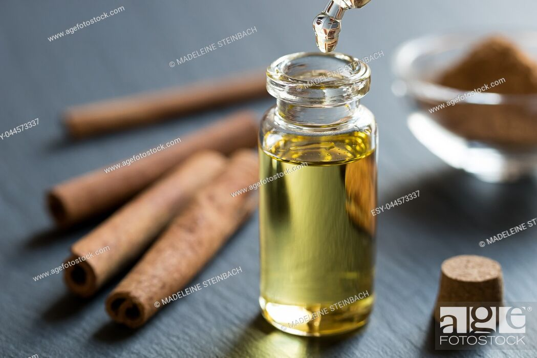 Stock Photo: A drop of cinnamon essential oil is being dropped into a bottle, with cinnamon sticks and powder in the background.