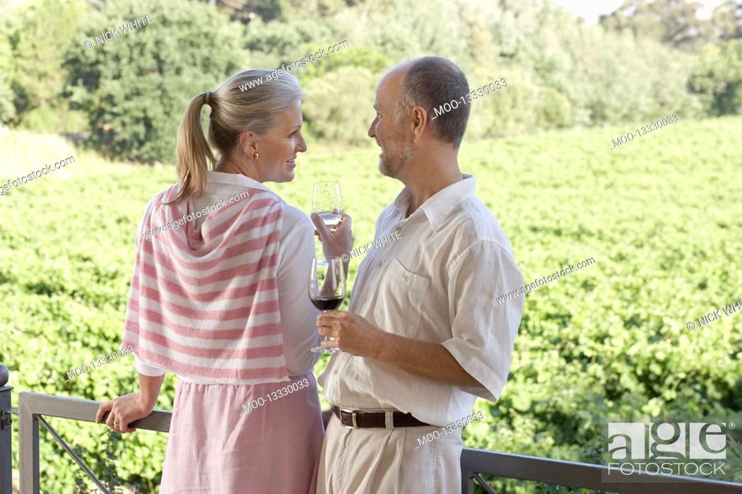 Stock Photo: Mature couple on terrace holding wine glasses.