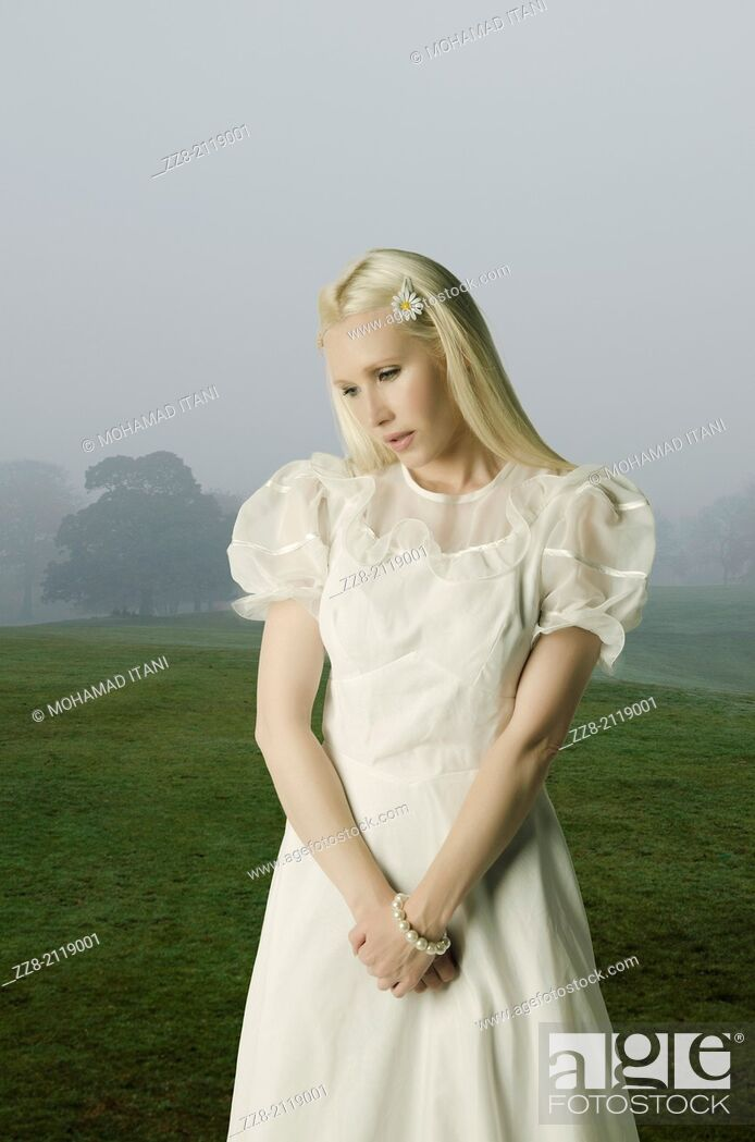 Stock Photo: Sad woman standing in a misty field.