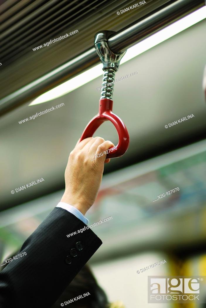 Stock Photo: A hand of a businessman inside MTR in Hong Kong, HKSAR.