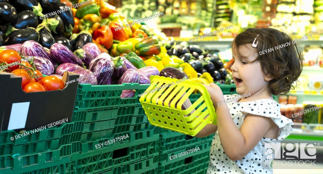 Stock Photo: Child shopping eggplants in supermarket. Concept for buying fruits and vegetables in hypermarket. Little girl hold shopping basket.