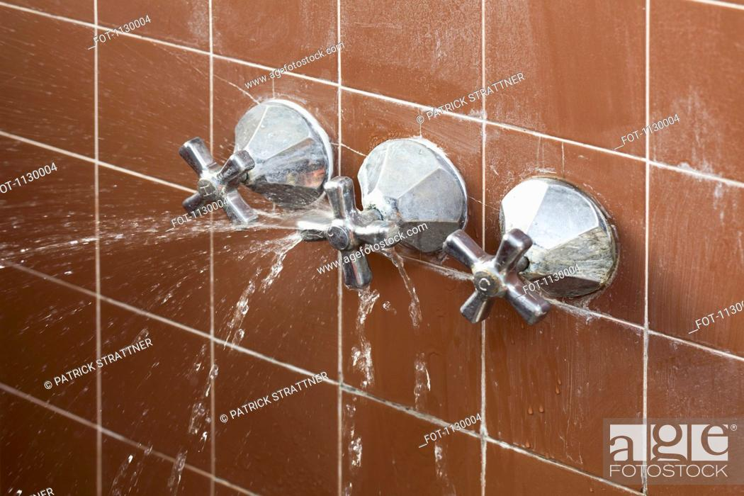 Stock Photo: A shower faucet handle spraying leaking water.