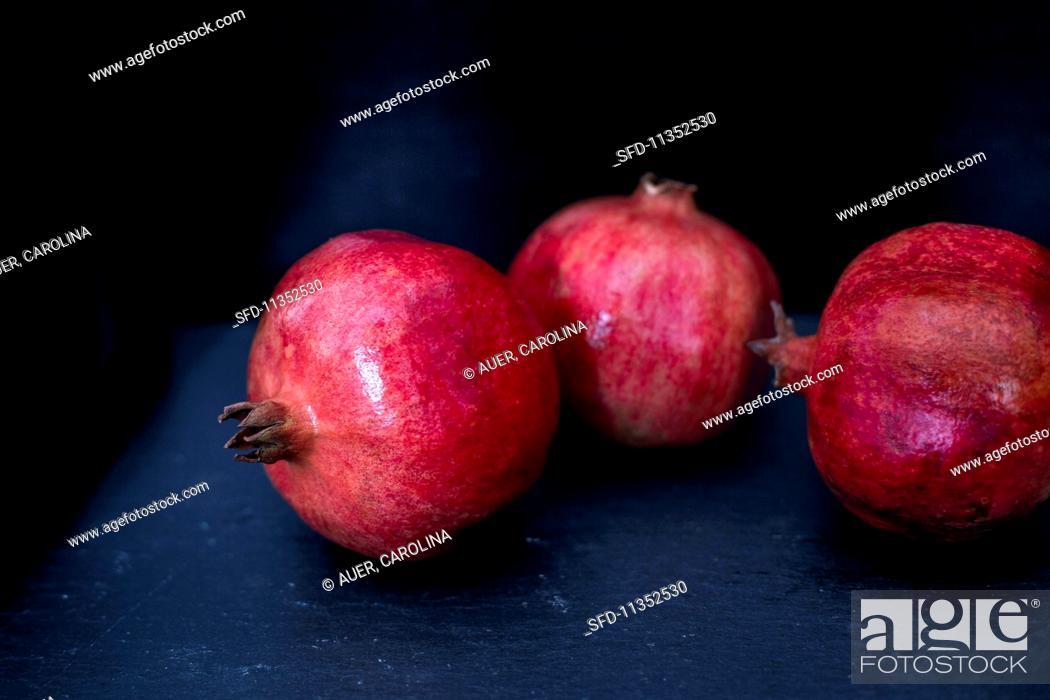 Stock Photo: Three pomegranates on a blue wooden table.