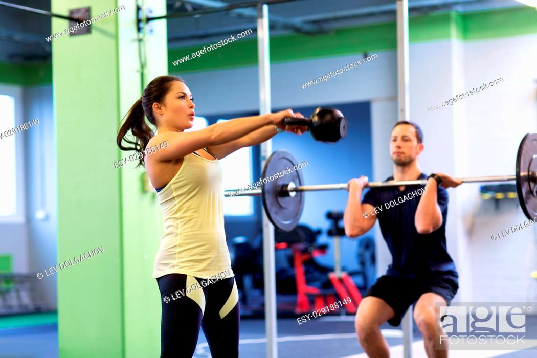 Stock Photo: sport, fitness, weightlifting, lifestyle and people concept - man and woman with kettlebell and barbell exercising in gym.