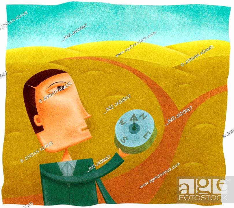 Stock Photo: A businessman holding a compass in front of a path that splits in two.