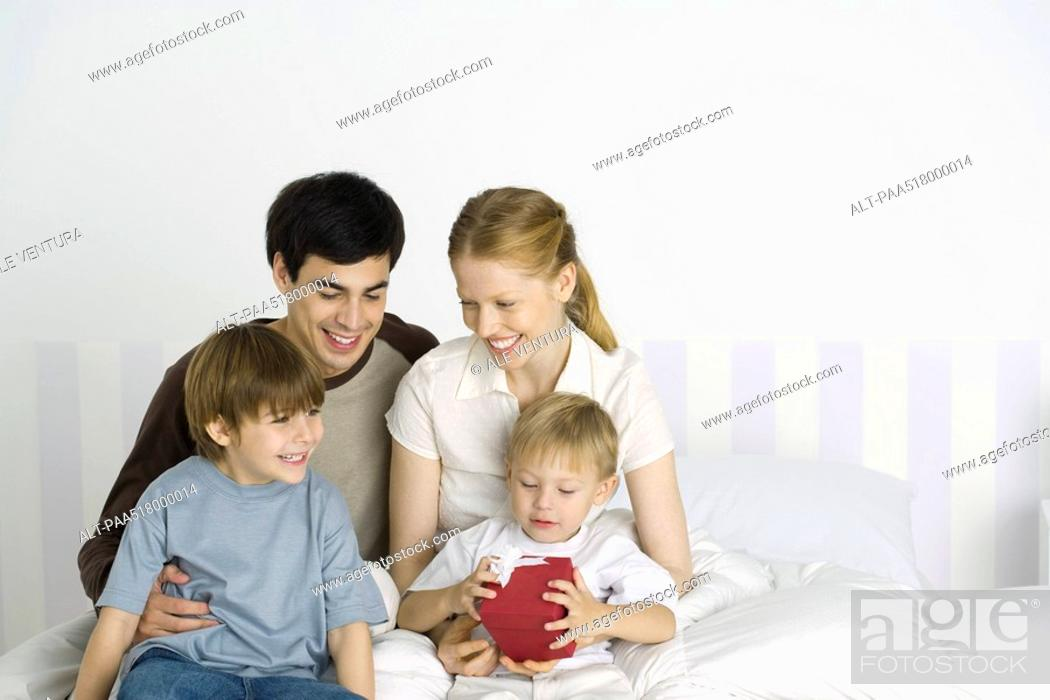 Stock Photo: Parents and two children sitting together on bed, one boy holding gift.