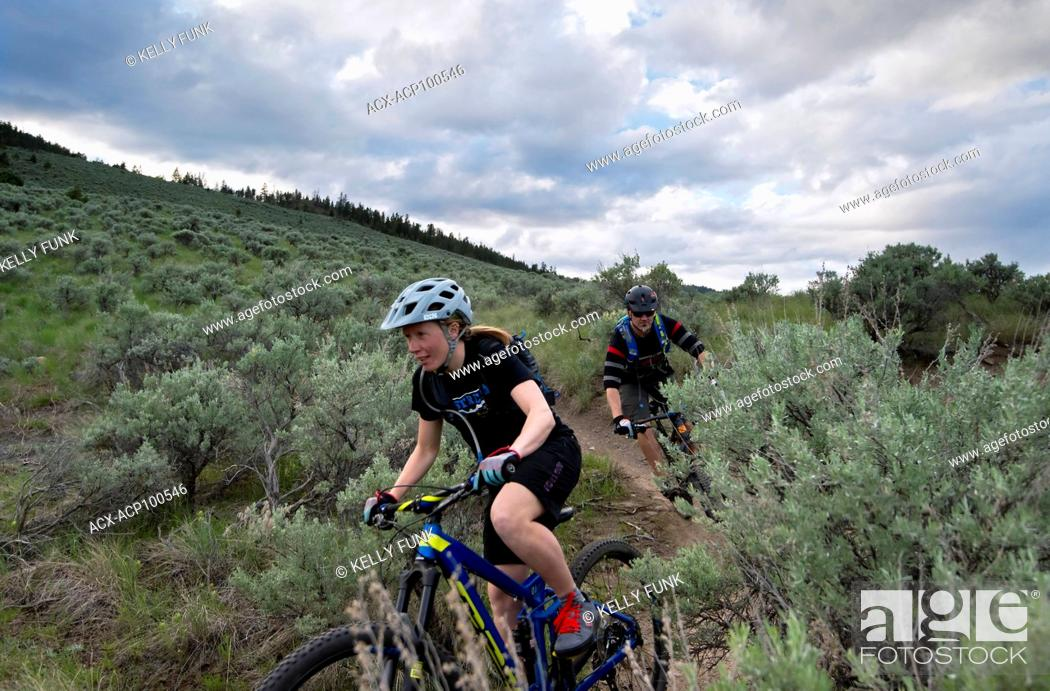 Imagen: A pair of mountain bikers enjoy the ride at sunset in the Lac Du Bois Protected Grasslands over Kamloops, Thompson Okanagan region, British Columbia, Canada.
