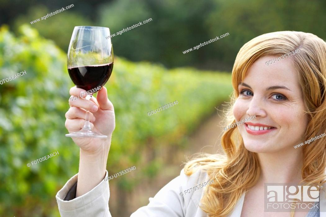 Stock Photo: Young woman holding glass of red wine in vineyard (portrait).