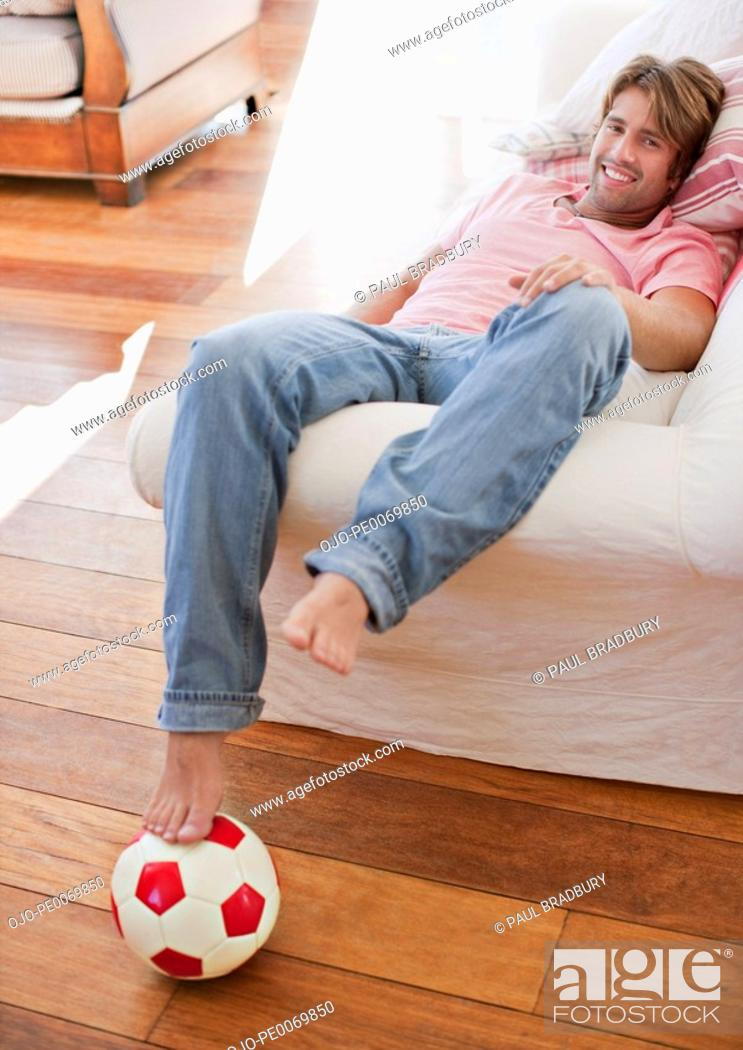 Stock Photo: Man laying on sofa with foot on soccer ball.
