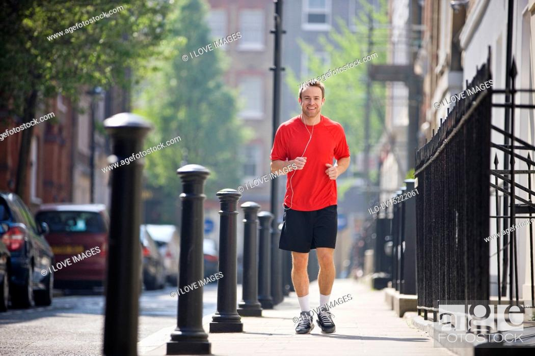 Stock Photo: A young man jogging in the street, listening to music.