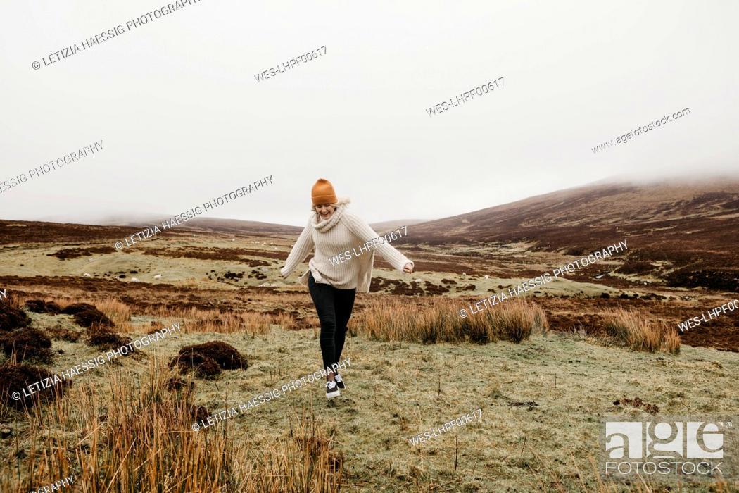 Photo de stock: UK, Scotland, Isle of Skye, happy young woman running in rural landscape.