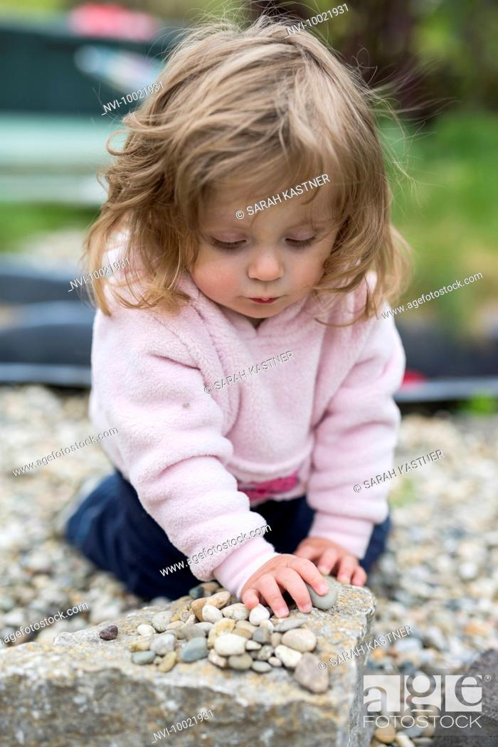 Stock Photo: Little girl playing with pebbles.