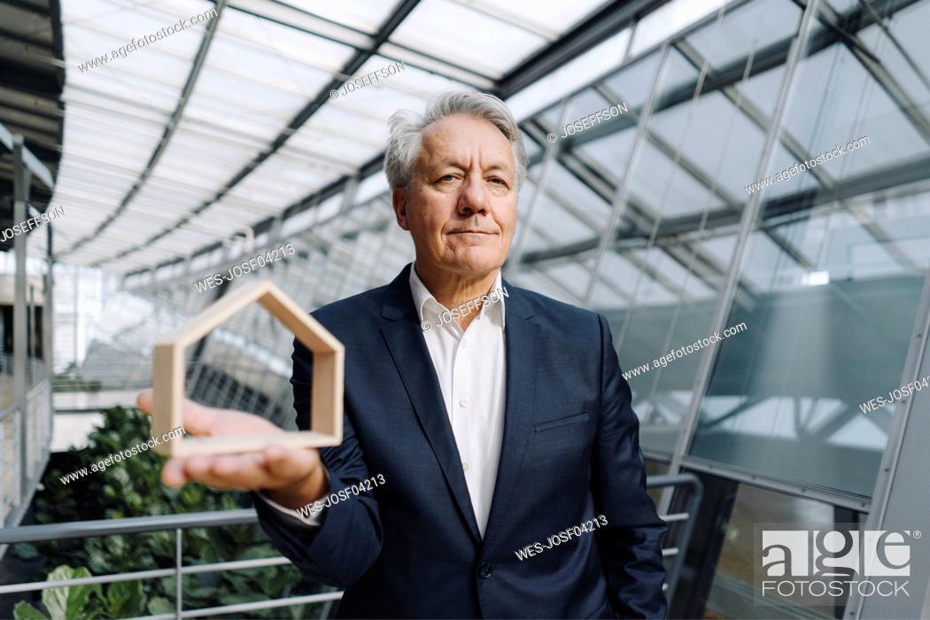 Imagen: Portrait of a senior businessman holding house model in office.