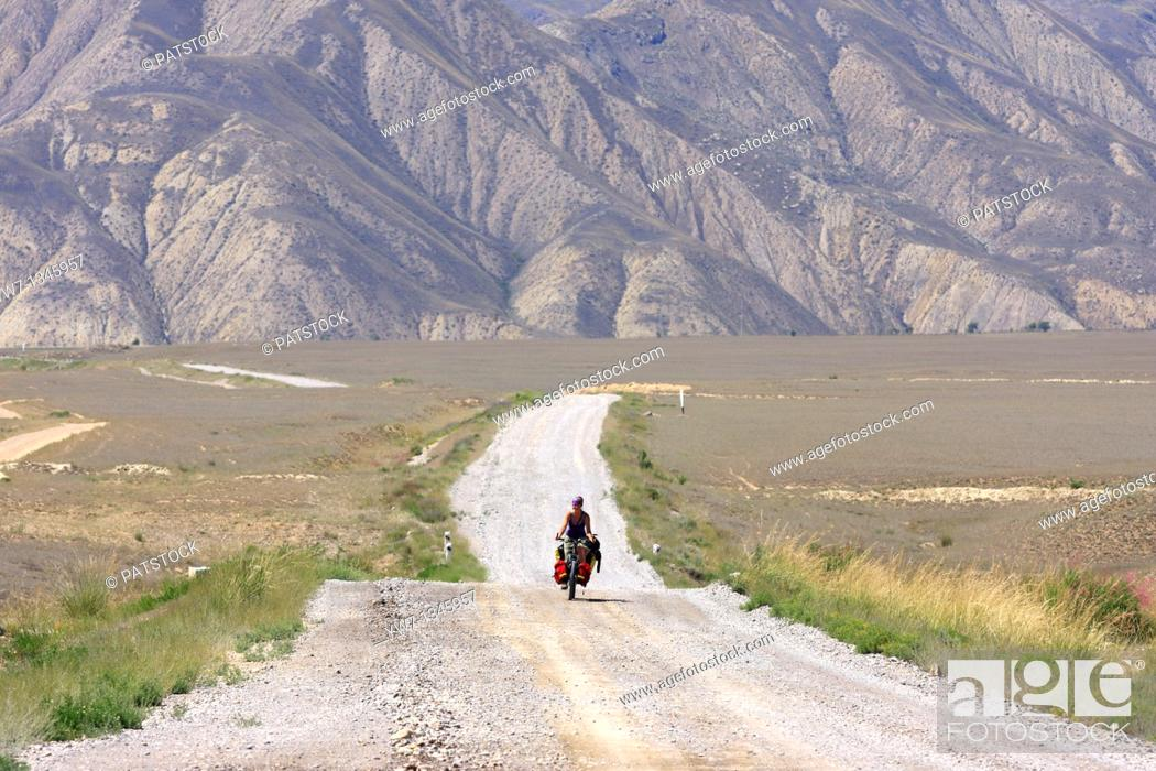 Stock Photo: Female cyclist on a mountain road, leading from Kazarman to Naryn, Kyrgyzstan.