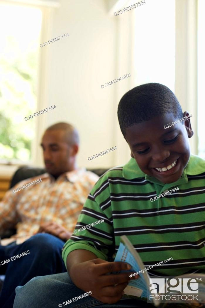 Stock Photo: Young boy reading book with man in background.