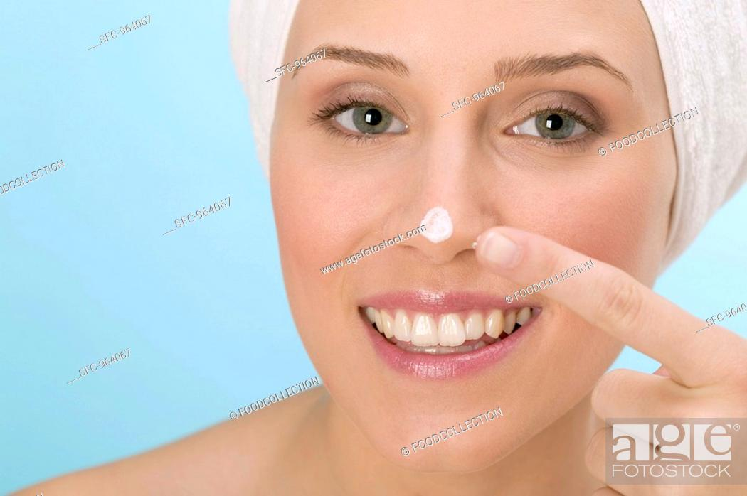 Stock Photo: Woman dabbing face cream on her nose.