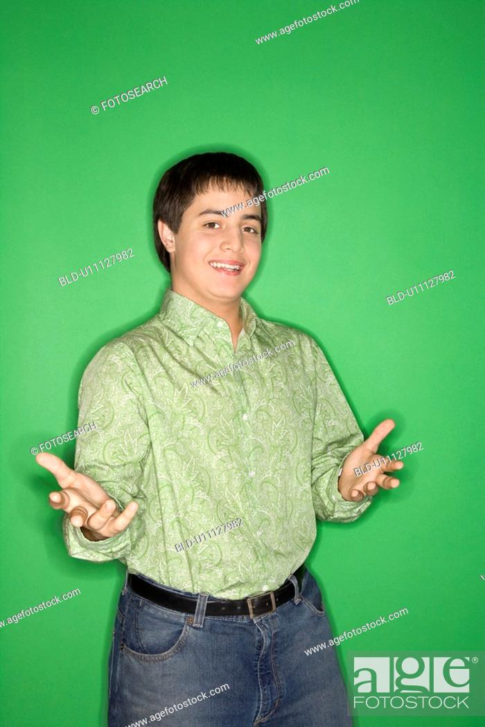 Stock Photo: Portrait of Caucasian teen boy with hands opened towards viewer standing against green background.