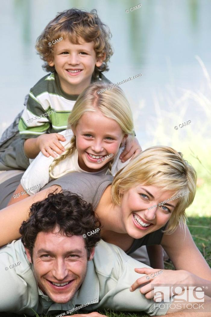 Stock Photo: Family with two children lying on grass, human pyramid, in front of lake.