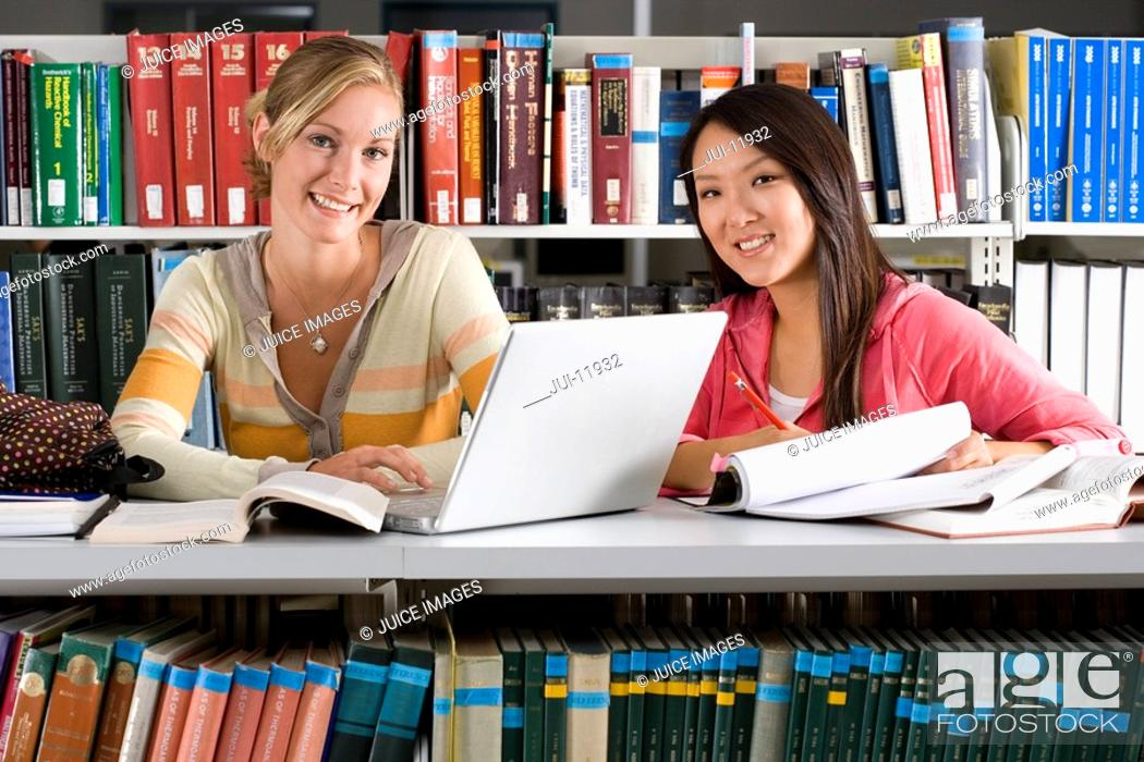 Stock Photo: Two women studying in library, smiling, close-up.