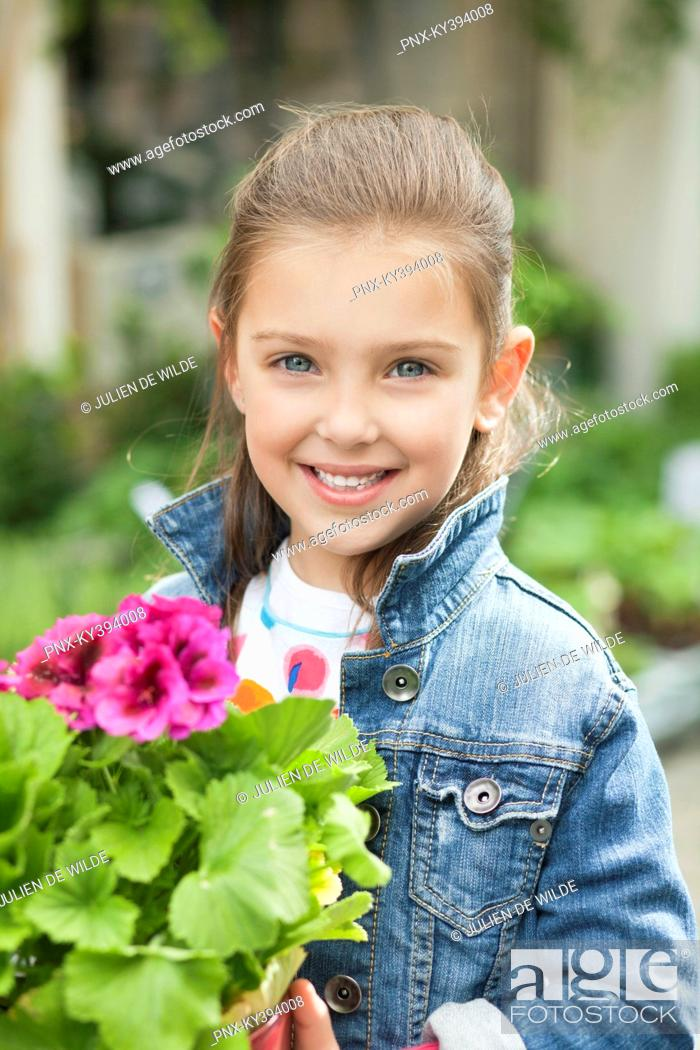 Stock Photo: Portrait of a girl holding a potted plant.