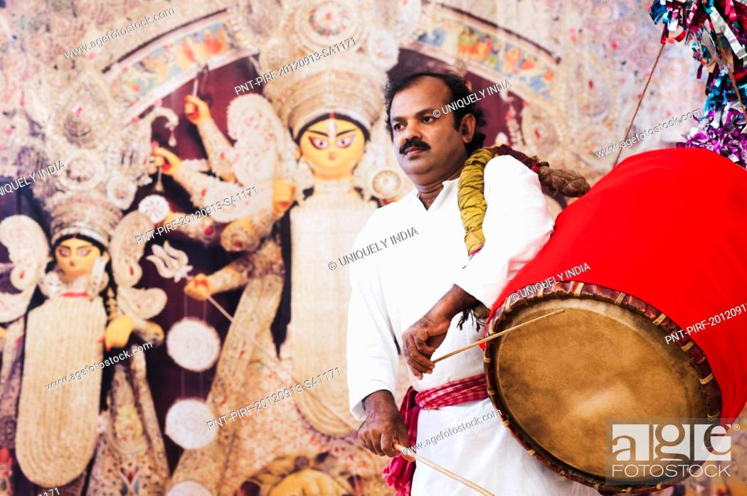 Imagen: Bengali man playing dhol (A large drum used to play during festival and celebration in India).