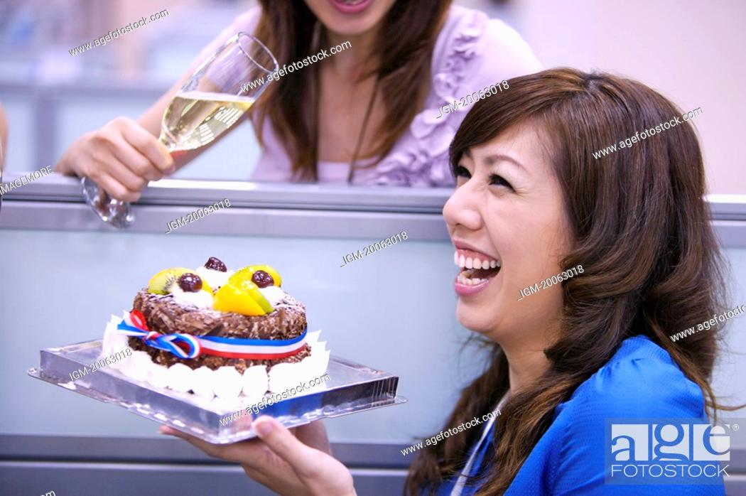 Stock Photo: Woman holding a cake and laughing happily.
