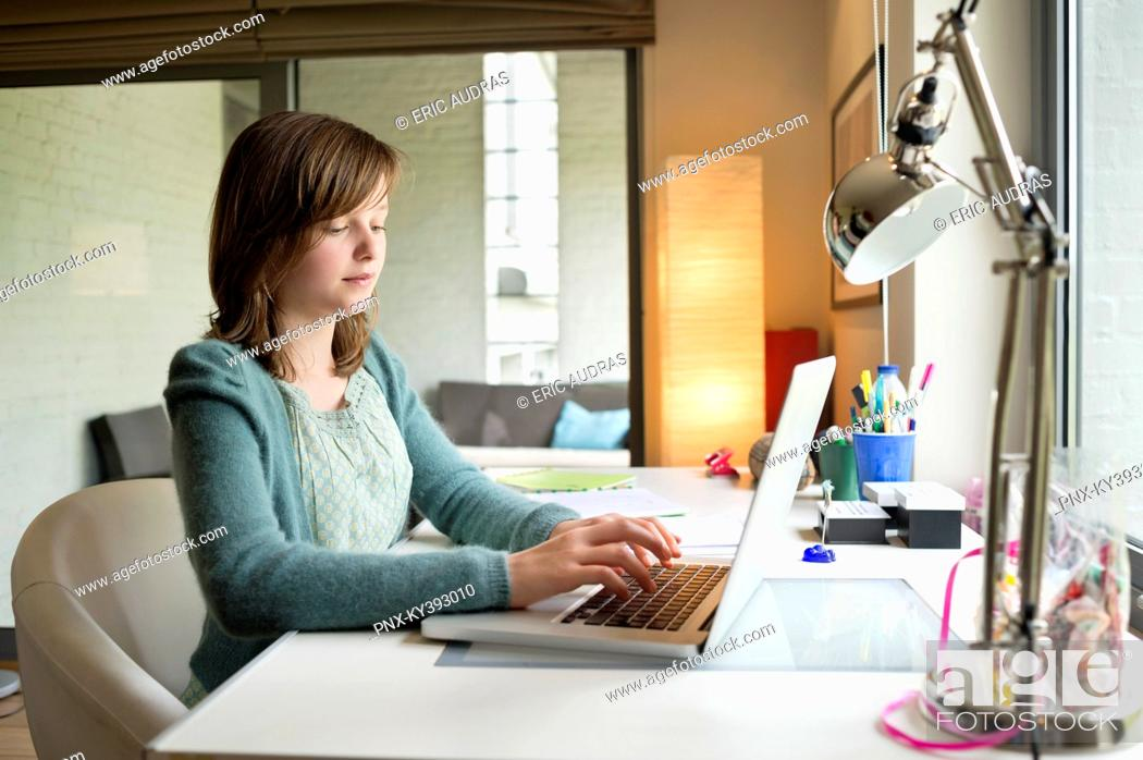 Stock Photo: Girl using a laptop at home.