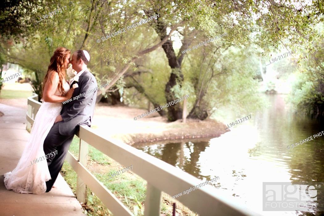 Stock Photo: Couple embracing, enjoying the moment and the beautiful lake scenery.