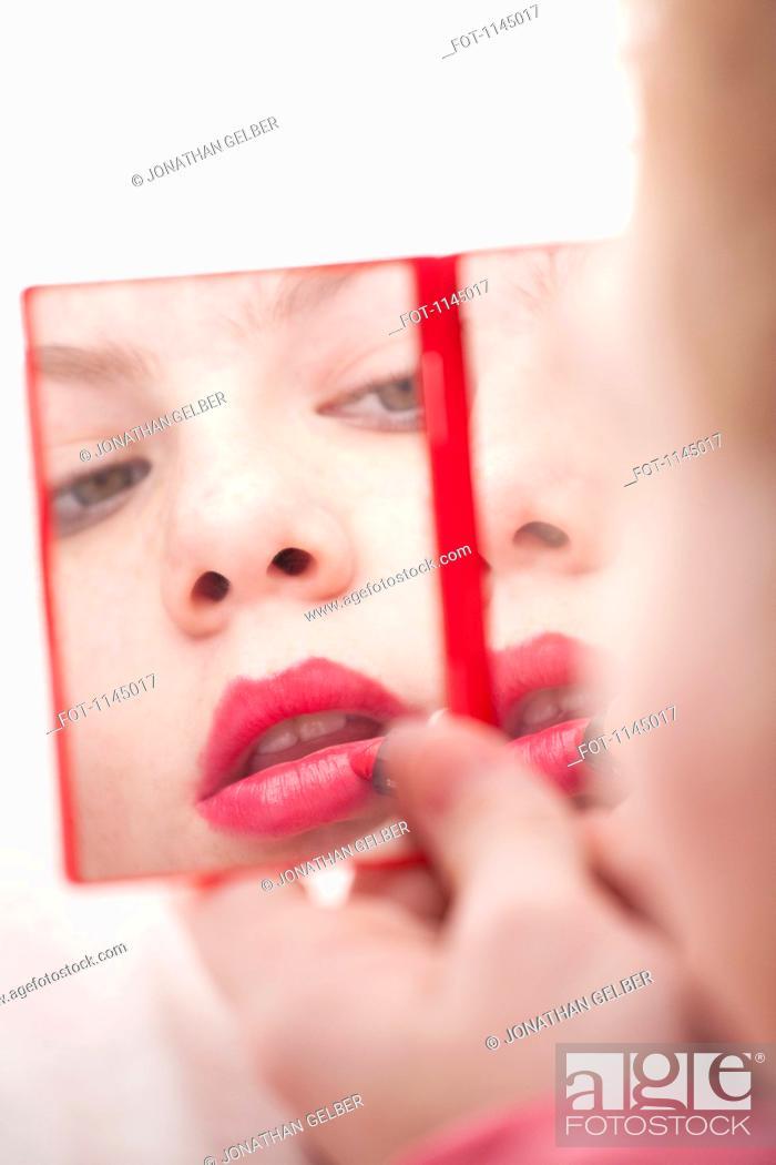 Stock Photo: Girl holding hand mirror and applying lipstick.