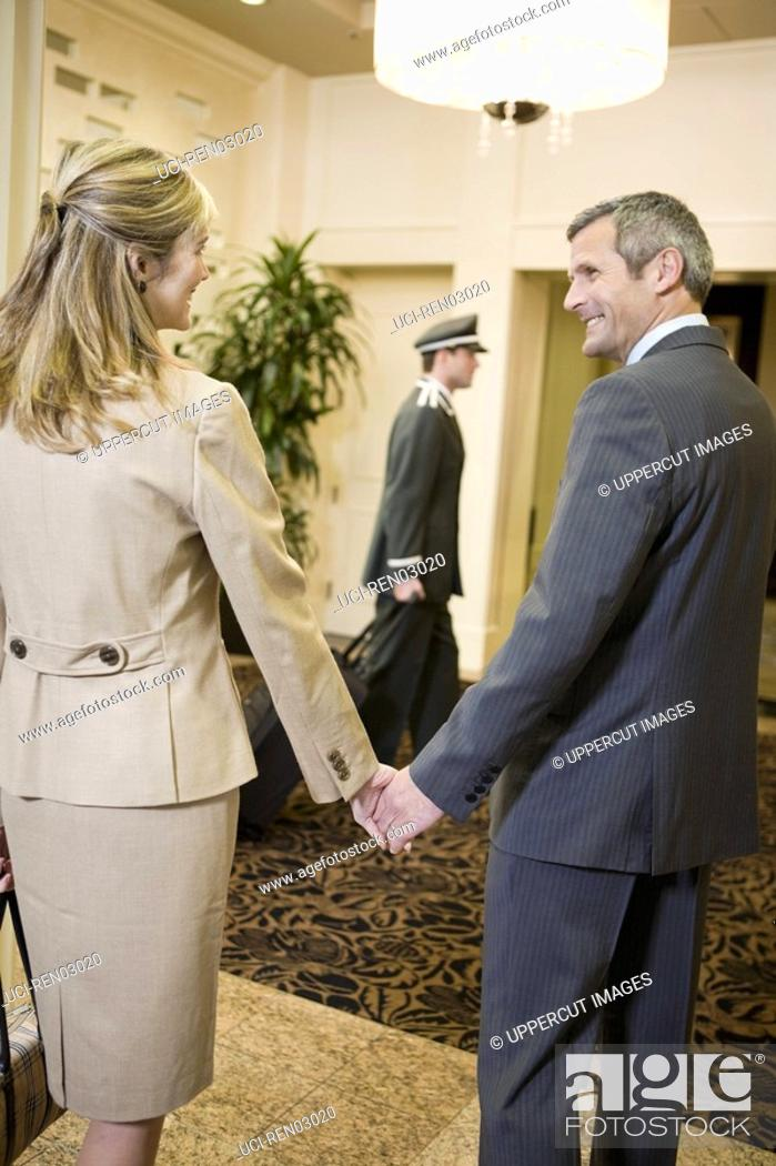 Stock Photo: Couple holding hands in lobby.