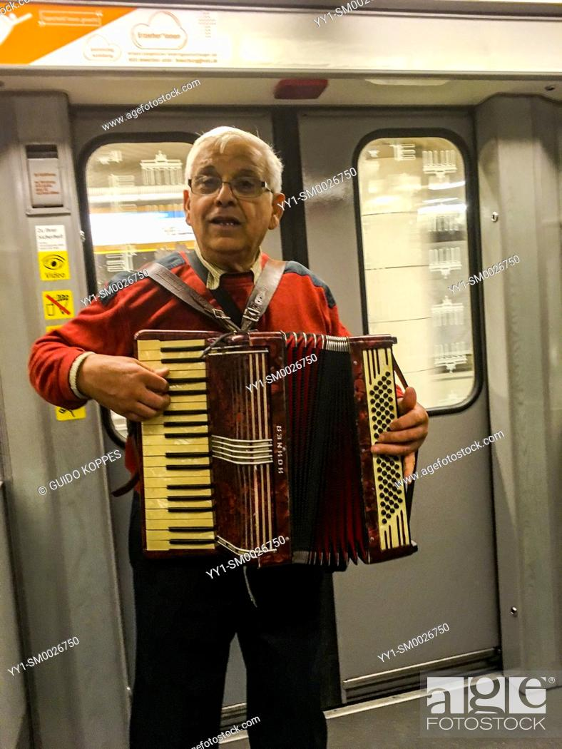 Stock Photo: Berlin, Germany. Musician playing his tunes inside the Berlin U-Bahn and underground subway.