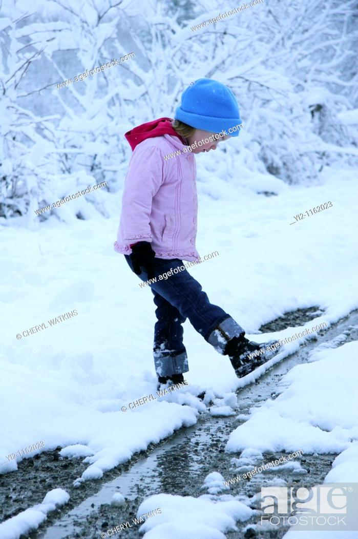 Stock Photo: A girl walking in snow.