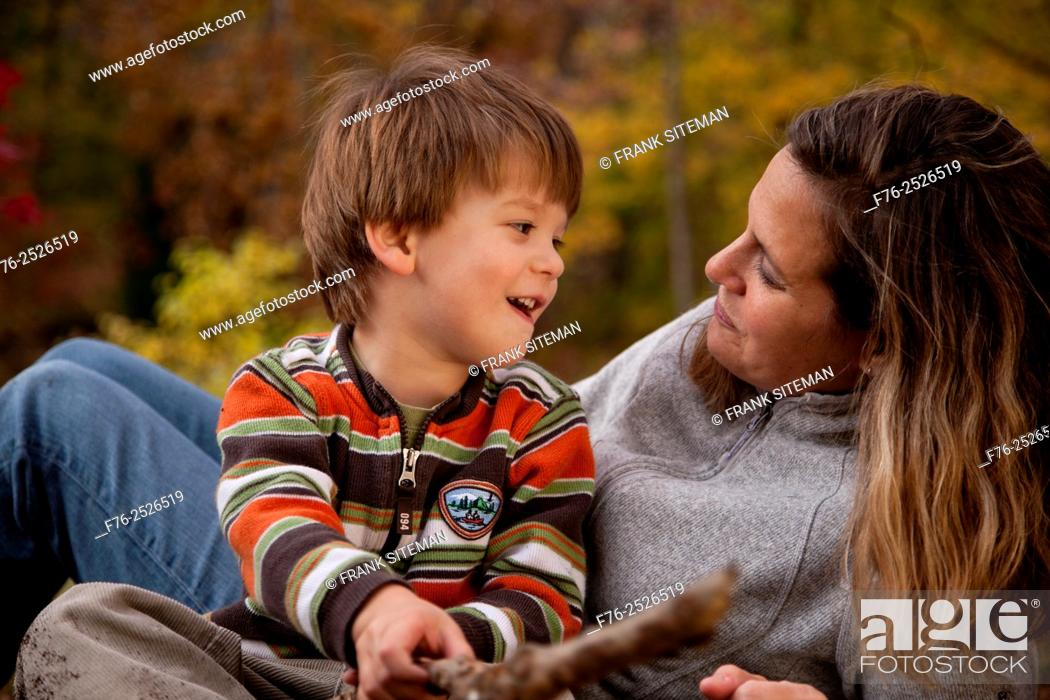 Stock Photo: Smiling mother, in her 30s, holding her three year old smiling son and holding her gaze with a loving look while reclining in their backyard in the fall with.