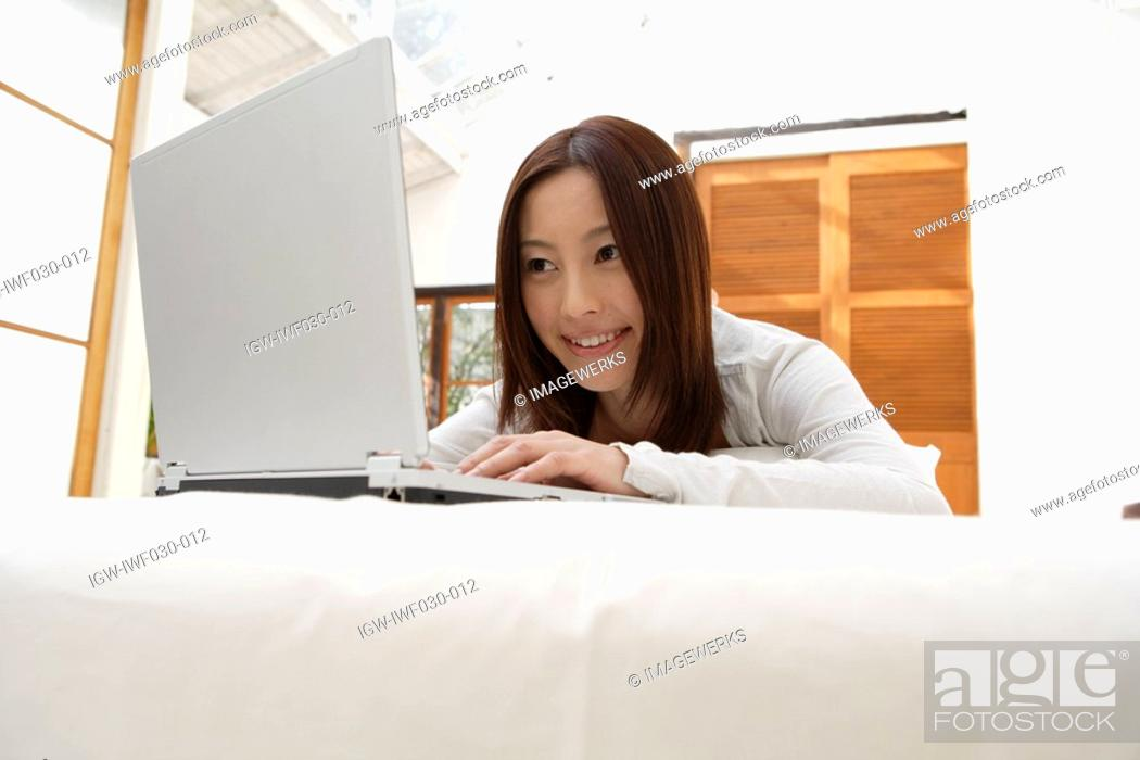 Stock Photo: A young woman using laptop.