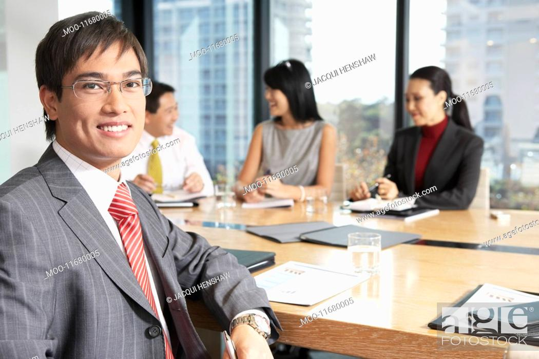 Stock Photo: Business man sitting at boardroom table with colleagues portrait.