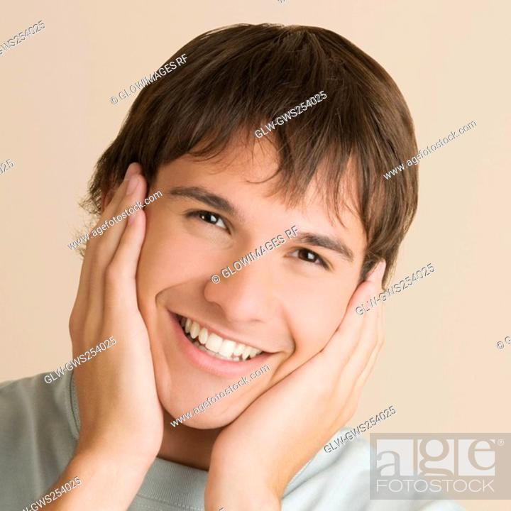 Stock Photo: Portrait of a young man with his head in his hands and smiling.