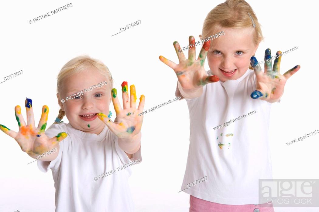 Stock Photo: Two blond girls with paint on their fingers.