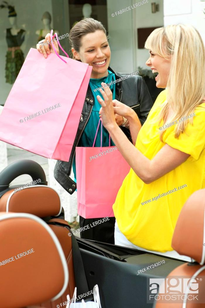 Stock Photo: Two women having fun near a car after shopping.