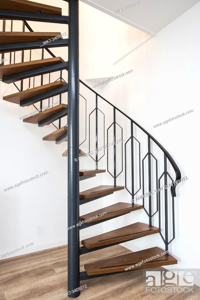 Stock Photo: Close up of a iron exterior spiral staircase on the side of a modern house with white wall clean.