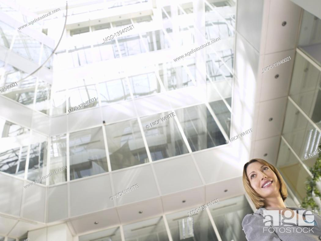Stock Photo: Business woman standing in atrium of office building low angle view.