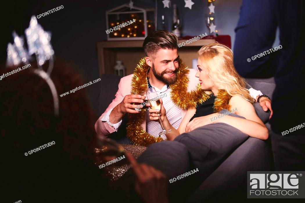 Stock Photo: Man and woman at party, sitting on sofa, holding drinks, making a toast.