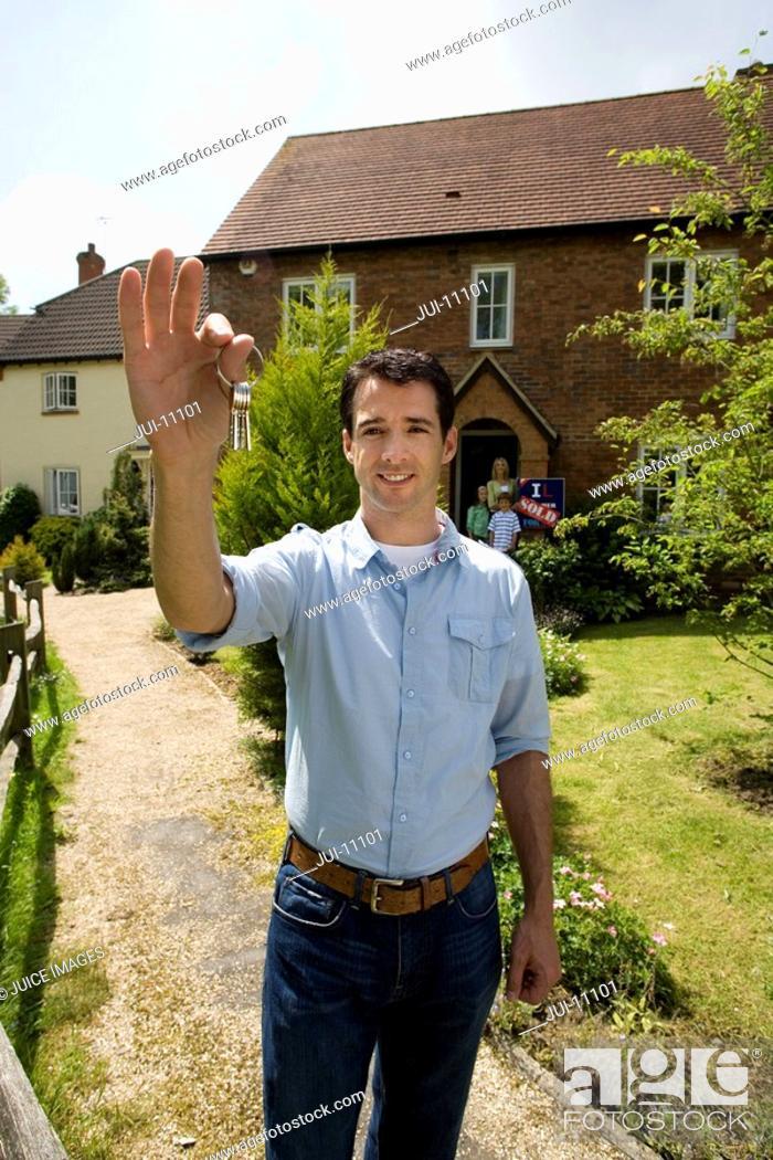 Stock Photo: Man holding up key outside house, portrait.