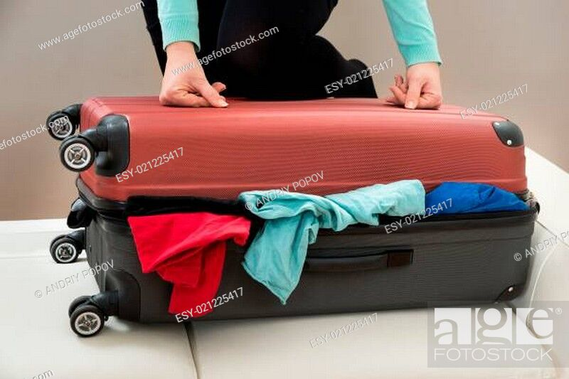 Stock Photo: Close-up Of Woman Trying To Close Suitcase With Excess Of Clothes.