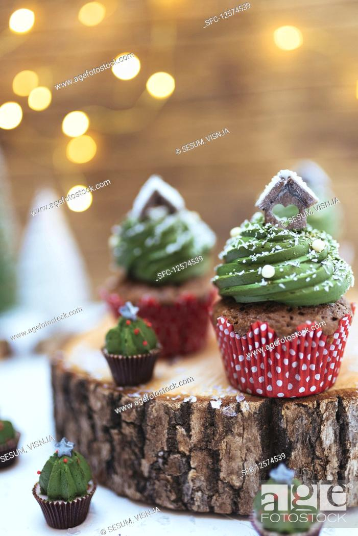 Stock Photo: Christmas chocolate muffins with creamy green frosting on a log slice.