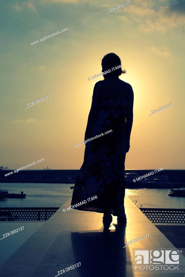 Stock Photo: Full length silhouette of a woman at sunset.