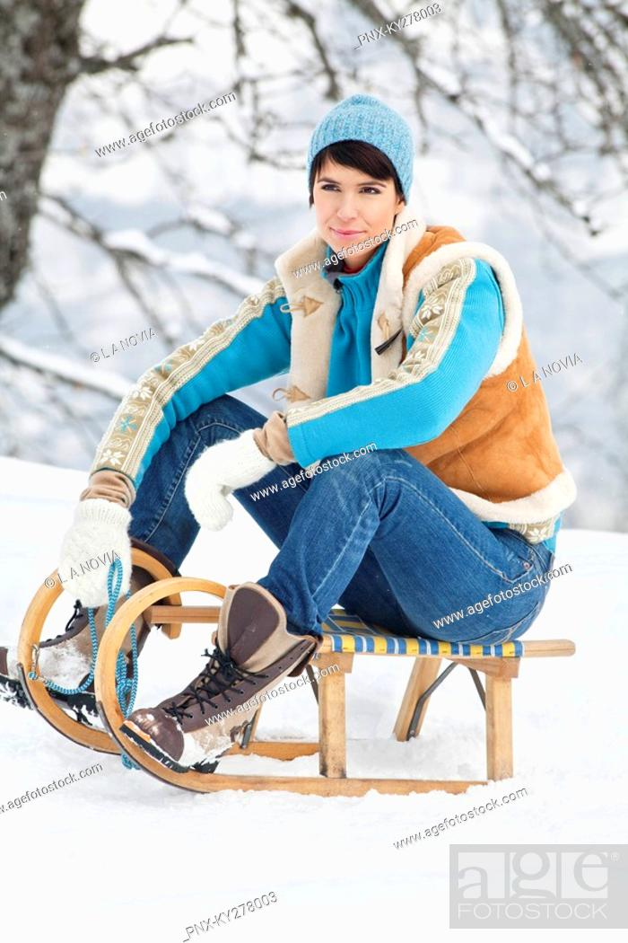 Stock Photo: Young woman sitting on sled.