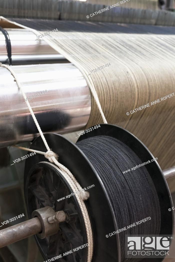 Stock Photo: Jacquard fabric loom with neutral and grey thread on reflective steel cylindars and dark metal industrial spool, La Manufacture de Roubaix, France.